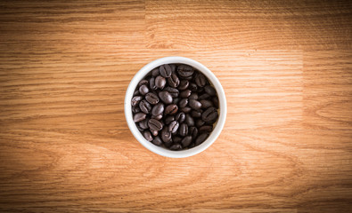 roasted coffee beans in white cup on wooden background