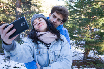 Couple of lovers enjoying in the snow doing a selfie. They are happy, spending a day of vacation in the mountains. - happiness, love, couple, time together concept