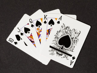 Royal flush of spades on black canvas