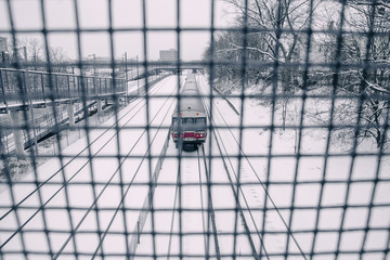 subway train going under the bridge. a train through the protective bars. winter landscape.  train passing under a pedestrian bridge. the concept of safety