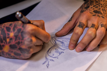 Male tattoo artist making sketch on paper, closeup