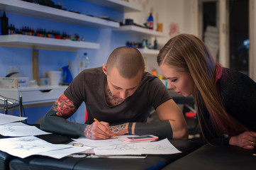 Male tattooer and client making design for tattoo