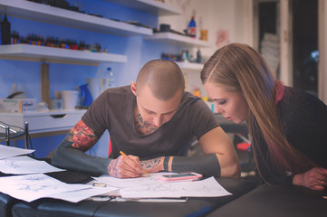 Male tattooist and client making sketch for tattoo