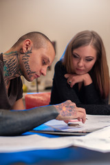 Male tattooist and blonde girl creating sketch
