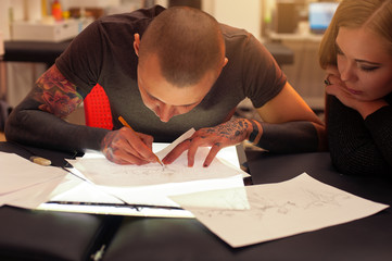 Male tattooer and client creating tattoo sketch