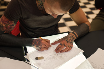 Young male tattoo artist creating sketch in parlor