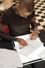 Young tattoo artist creating sketch for client