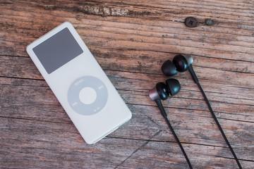 MP3-Player und Ohrhörer auf rustikalem Holzuntergrund, Draufsicht