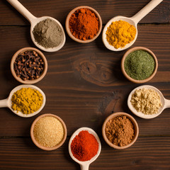 Foto op Canvas Kruiden Different spices in bowls and mixing spoons - Top view