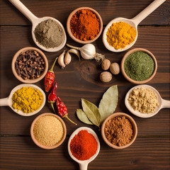 Foto op Canvas Kruiden Various spices in bowls and mixing spoons - Top view