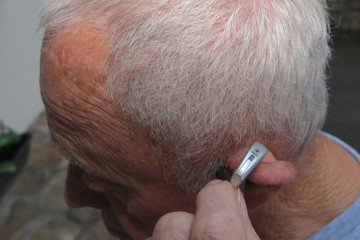 An assistant helps an elderly man put his hearing instrument to deaf