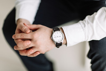 watch with white dial on the hand of a man in a white shirt