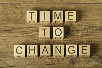 time to change text on a wooden cubes on a wooden background