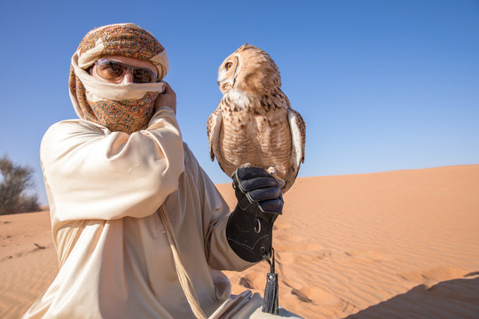 Young male pharaoh eagle owl (bubo ascalaphus) with a traditionally dressed arab male during a desert falconry show in Dubai, UAE.