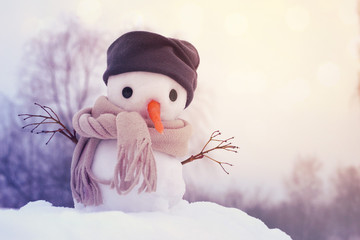 Small snowman in a cap and a scarf on snow in the winter against the background of trees. Festive background with a lovely snowman. Christmas Card, copy space
