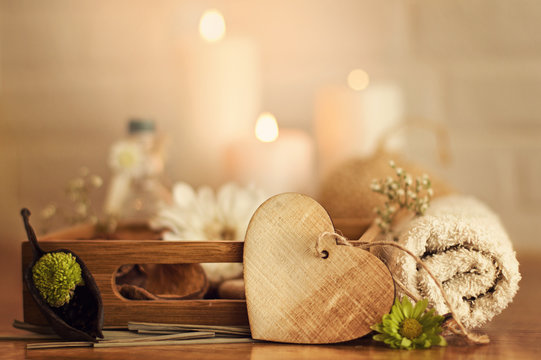 Spa setting with towels, oil and wooden heart on white bricks background