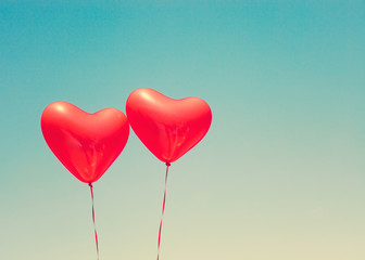 Two red heart shaped balloons in flight