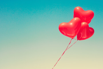 Various red heart shaped balloons in flight