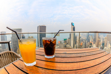 aerial view of city skyline and cocktail from the top of a modern skybar in the city.