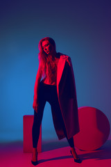 Fashion portrait of young girl in coat of black pants and heels in the studio with color filters. fashion concept