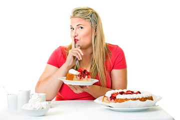 Guilty fat woman eating a slice of cream cake.