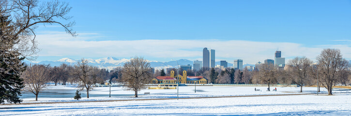 Winter at Denver City Park - A panoramic winter scene at a snow-covered city park, Downtown Denver, Colorado, USA.  Denver Skyline and snow-capped Mount Evans are rising high in the background.
