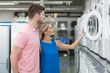 Couple At Groceries Store Buy Washing Machine