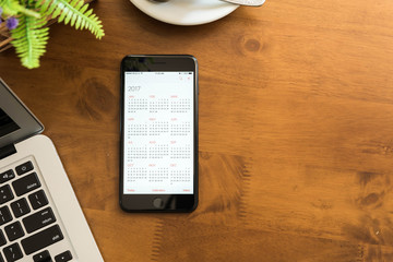 Hand of man use smartphone show calendar of 2017 on screen