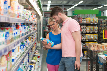 Couple At Groceries Store Buy Milk