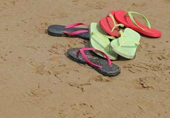 Colourful flip flop thongs on a sandy beach