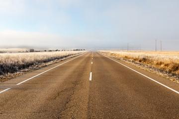 Carretera de asfalto, praderas y niebla.