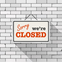 """Simple white sign with text """"Sorry we're closed"""" hanging on a gray brick wall. Grunge brickwork background, textured rough surface. Creative business interior template for shop, store, supermarket."""