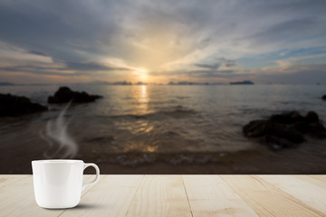 Hot coffee cup with steam on wooden table top on blurred golden sunrise background