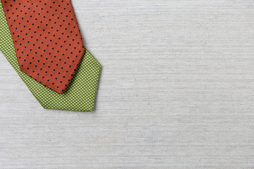 Green and red necktie on canvas texture background, Christmas concept