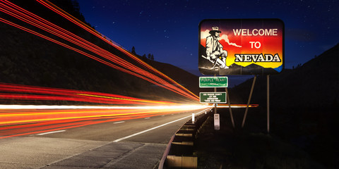 Nevada State line road sign with long exposure traffic trails at night.