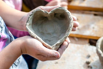 The child shows heart made with his own hands from white clay