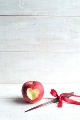 ハート型に皮を剥いた林檎と赤いリボンのナイフ