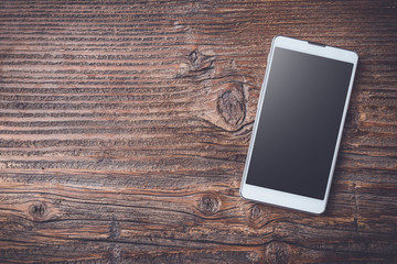 White smart phone on an old wooden table