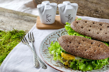 Healthy food - sandwiches of dark bread and poached eggs.