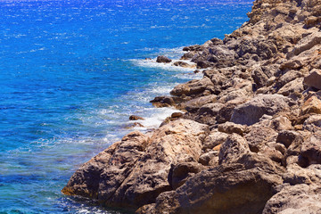 Stones along the seashore. Blue seawater. Small waves beating against the shore. Unapproachable deserted stony shore in the region Lenta on the island of Crete