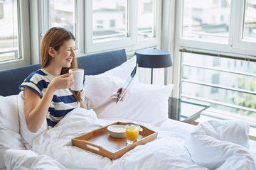 Beauty woman sitting on bed, eating breakfast, reading tablet