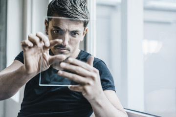 Man using transparent mobile device