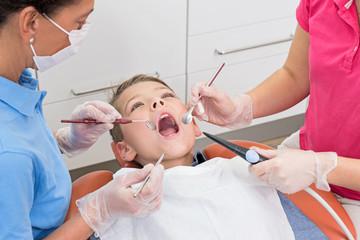 Junge liegt mit offenem Mund auf Zahnarztstuhl bei Untersuchung