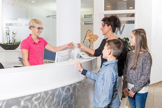 Mutter mit Kindern im Empfangsbereich einer Zahnarztpraxis
