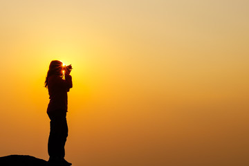 Silhouette of women is taking some photograph on mountain at sunset.