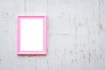 Pink photo frame over white rustic wooden background