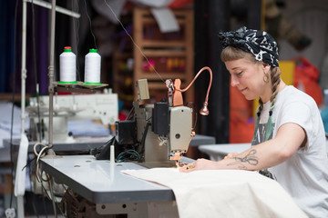 Young tattooed seamstress sewing in a factory environment