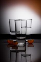 Three glasses of water on orange background with mandarin