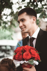 stylish brunette smiling groom in a suit  holds a luxurious bouq