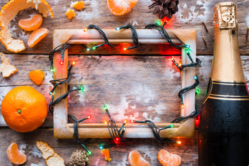 Christmas frame with a garland, champagne and tangerines